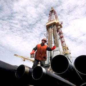 Oil Field worker on oil pipes in front of oil rig