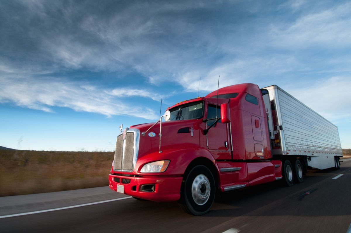 DOT red semi truck driving across the country