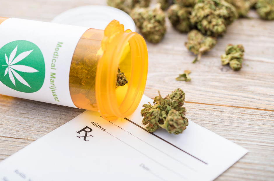 Marijuana buds spilling out of prescription bottle on top of Rx pad